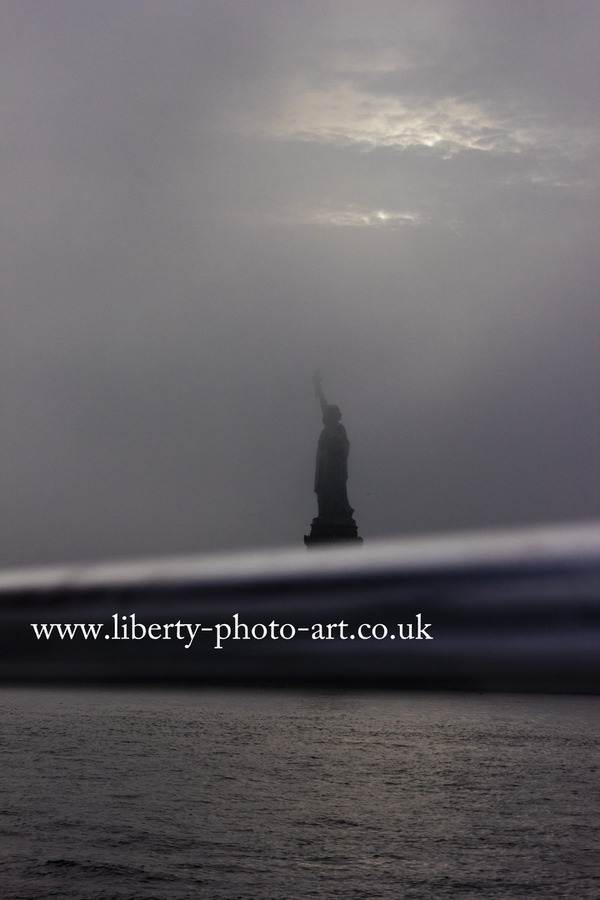 Striking view of Liberty Enlightening the World (Statue of Liberty) in dense mist, New York City