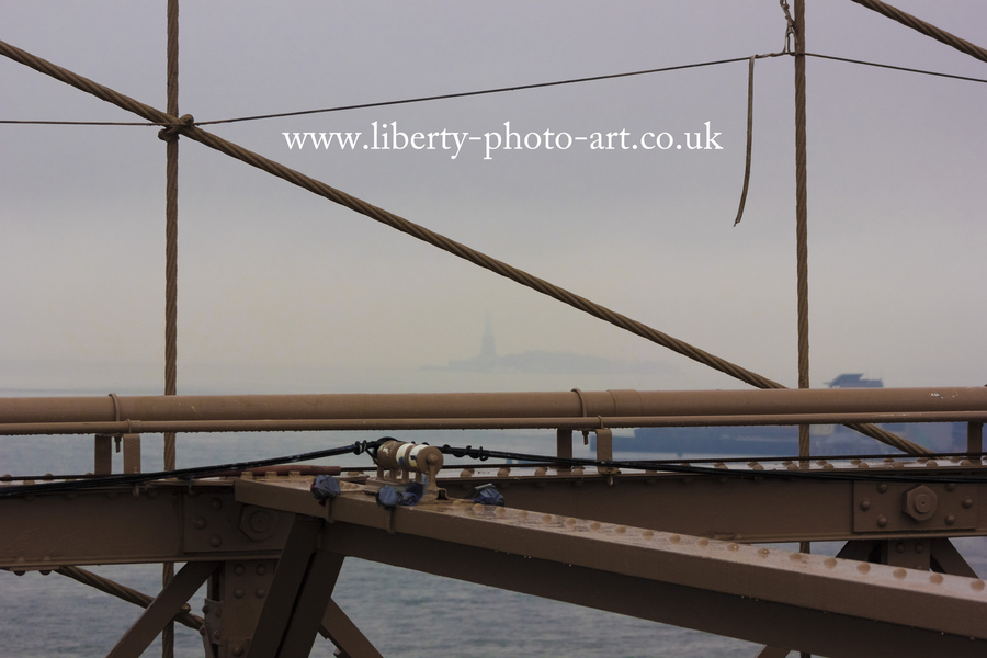 Creative view from inbetween steelwork of the Brooklyn Bridge looking along the East River towards Lady Liberty (Statue of Liberty) shrouded in fog in the distance, New York City